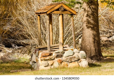 Wood and stone well on historic site of Hayden Log Cabin in Mammoth Lakes, California.