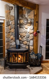 Wood stove fireplace with metal body and glass door in house with cozy interior