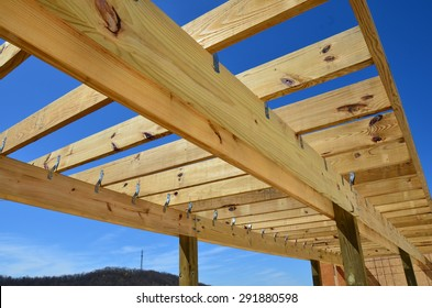 Wood structure framing for a pergola against a blue sky