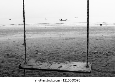 Wood swing hanging from a tree on the beach over blurred  fisherman and boat. Black and white tone. Can used for concept of lonly time.