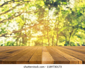 wood table and Abstract blur image of green tree bokeh with sun and sunlight for background usage.