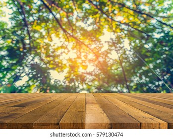 wood table and Abstract blur image of green tree bokeh for background usage .