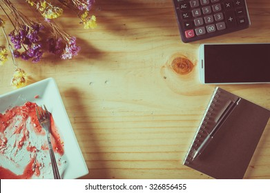 Wood table background with blank area for text or message, dirty dessert plate, flowers, calculator and smartphone as frame around in afternoon time with film filter effect