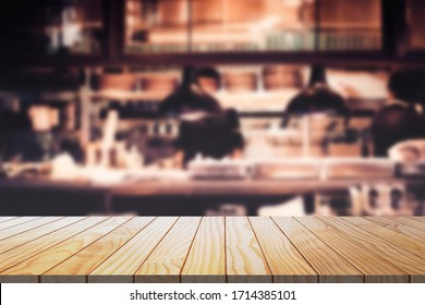Wood table background with blurred restaurant kitchen.