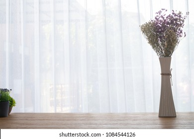 Wood table with Beautiful Gypsophila dry flower in tall vase on white curtain background texture at living room in morning.