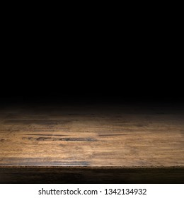 wood table at black background.Brown hardwood desk perspective for display or montage of product,Mock up template for your design