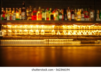 wood table with blur alcohol drinking bottle and glasses in the bar or pub at night background