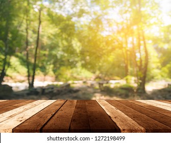 wood table and blur image of Abstract Bokeh of green tree with sun for background usage.(vintage tone)