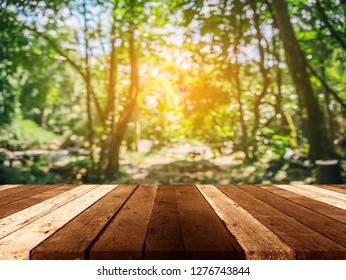 wood table and blur image of Abstract Bokeh of green tree forest with sun for background usage.(vintage tone)