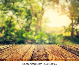 wood table and blur image of Abstract Bokeh of green tree with sun rays for background usage.