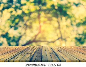 wood table and blur image of Abstract Bokeh of green tree with sun for background usage.