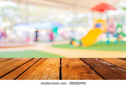 Wood table and blur image of children's playground at public park for background usage.