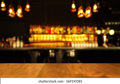 wood table with blur light of lamp and bar or pub with alcohol bottle for party abstract background