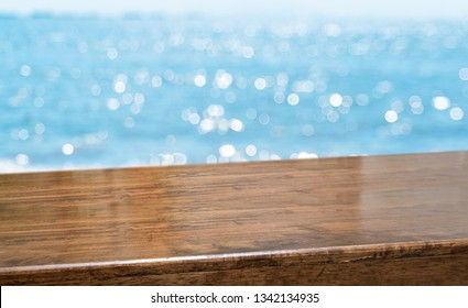 Wood table at blur sea view.Empty brown glossy wood table top with blur sky and sea boekh background,banner mock up template for display of product