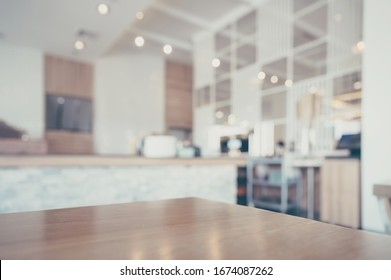 Wood table and blurred coffee shop interior background and lighting bokeh