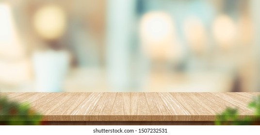 wood table and blurred leaf foreground in restaurant with bokeh background. product display template.Business presentation