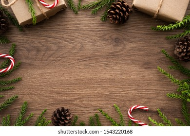 Wood table with Christmas decoration including giftbox, candy cane, pine branches and pine cones. Merry Christmas and happy new year concept. Top view with copy space, flat lay.