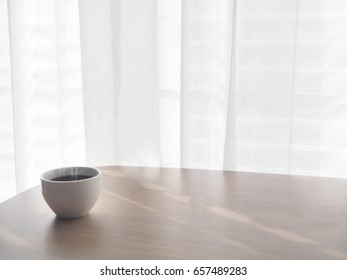 wood table with copy space for text and coffee cup of cappuccino on blurry white drape texture background, view from front wood table.