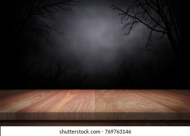 wood table in the dark whit silhouette dead tree at night background.