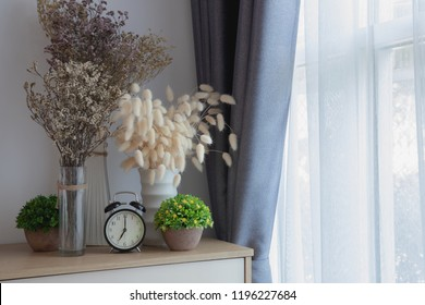 wood table with decoration flowers on white curtain window texture background.