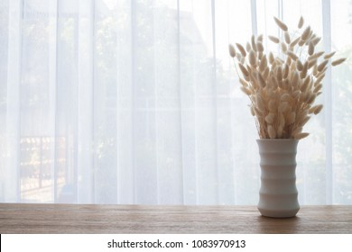 Wood table with Dry Rabbit tail Flower in White High vase on white curtain background texture at living room in morning.
