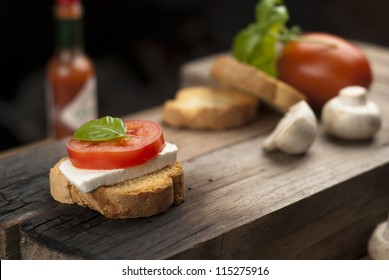 wood table with an italian antipasto, with fresh cheese, tomato and basil