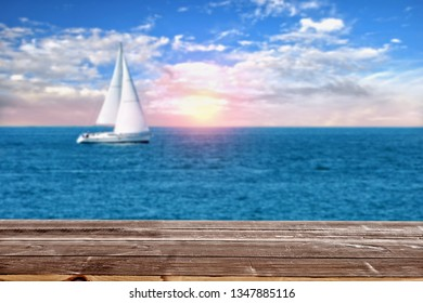 wood table looking at ocean with sunset and a sailboat