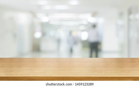Wood table in modern hospital interior with empty copy space on the table for product display mockup. Medical and healthcare concept.