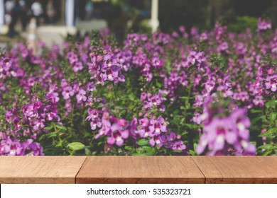 wood table for montage or display your product with blur background of blooming pink purple flower in flowerbed in field at garden park