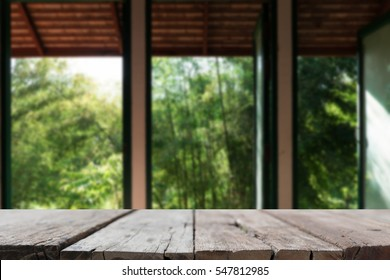 wood table for montage or display your product with background of three large opening window with bamboo tree garden view