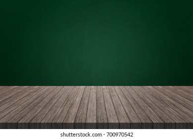 Wood table on blank green chalkboard background with a space for text. For your product placement or montage with focus to the table top in the foreground. Empty wood brown shelf