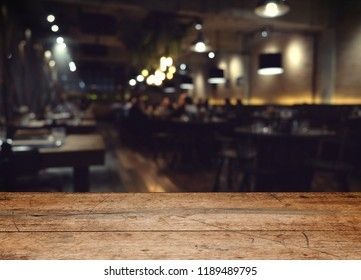 wood table on blur of cafe, coffee shop, bar, resturant, background - can used for display or montage your products