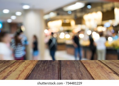 wood table on blur image people in shopping mall with bokeh