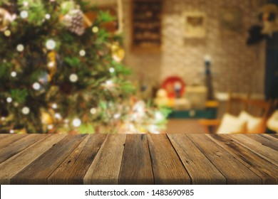 Wood table over Christmas tree with decoration blur background. can be used for display or montage products.