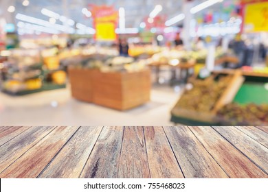 Wood table over Supermarket with fresh fruits and vegetable on shelves in store blurred grocery background, product display