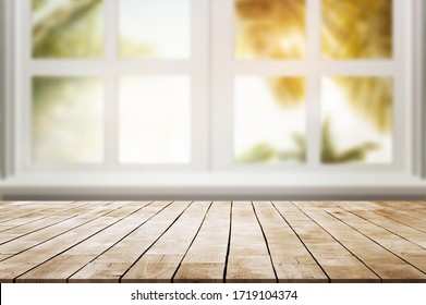 wood table place and window with  palm leaves against with sun light