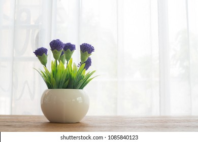 wood table with purple flower on ceramic pot and white curtain window  texture background.