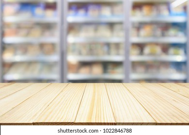 wood table with supermarket commercial refrigerators freezer showing frozen foods abstract blur background