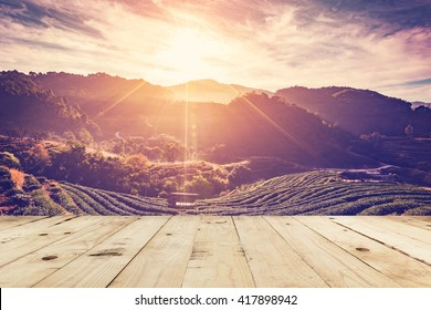 wood table and tea field and sunrise vintage in morning