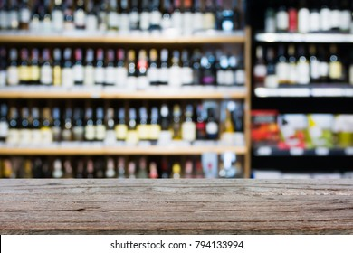 Wood table top with Abstract blur wine bottles on liquor alcohol shelves in supermarket or wine store background