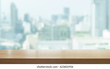 Wood table top against the background blurred buildings in the city.. - For product display and advertising and promotional purposes.
