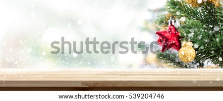 Wood table top banner background with snow and ornaments on Christmas tree