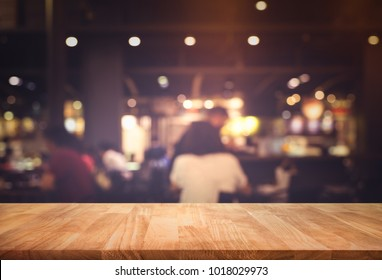 Wood table top (Bar) with blur people siting night cafe,restaurant background .Lifestyle and celebration concepts ideas