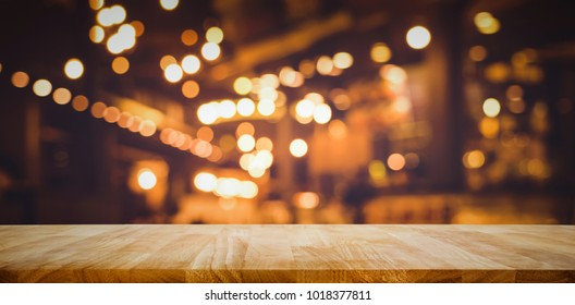 Wood table top (Bar) with blur light bokeh in dark night cafe,restaurant background .Lifestyle and celebration concepts ideas