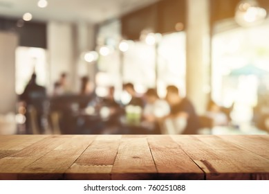 Wood table top with blur cafe interior and people in background  - can be used for display or montage your products (food)