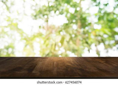 Wood table top and blur of fresh green bokeh from garden backgro