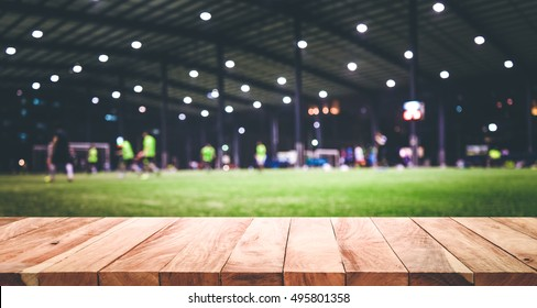 Wood table top with blur indoor football (soccer) field background.For montage product display or design key visual layout  background.