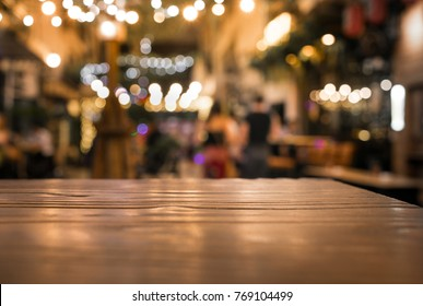 Wood table top with blur of lighting in night cafe restaurant (community) background/selective focus.
