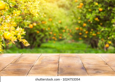 Wood table top with blur of orange garden in the morning.For montage product display.