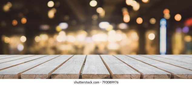 Wood table top and blurred bokeh cafe and restaurant banner background with vintage filter - can used for display or montage your products.